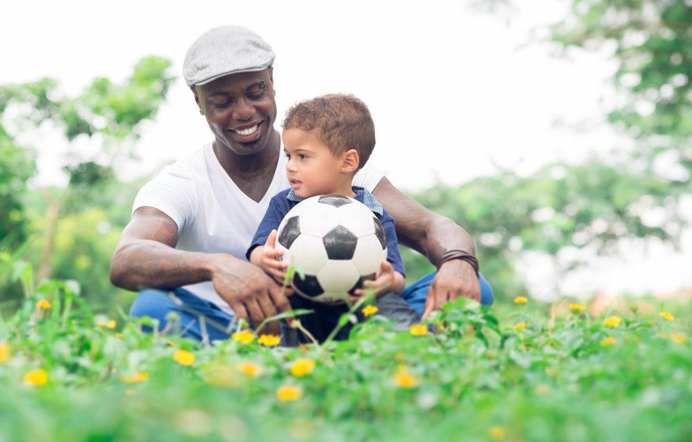 Un padre con su hijo pequeño con una pelota de fútbol sentados en la hierba
