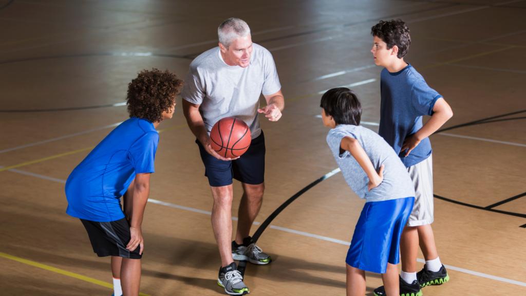 Entrenador habla a tres jugadores de baloncesto. Los retos del entrenador de Minibasket