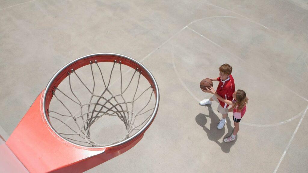 Dos jugadores con un balón y una canasta en vista desde el tablero. Los retos del entrenador de Minibasket